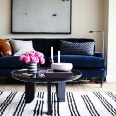 Chic Midcentury Modern Living Area Features Navy Sofa Striped Rug