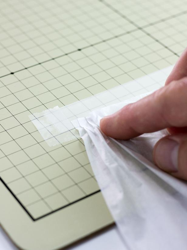 "Cut a 7"" x 20"" piece of tissue paper. Attach the 20"" side of the tissue paper to the upside-down tape strip by pressing 1/4"" folds onto the adhesive, overlapping the folds as you go."