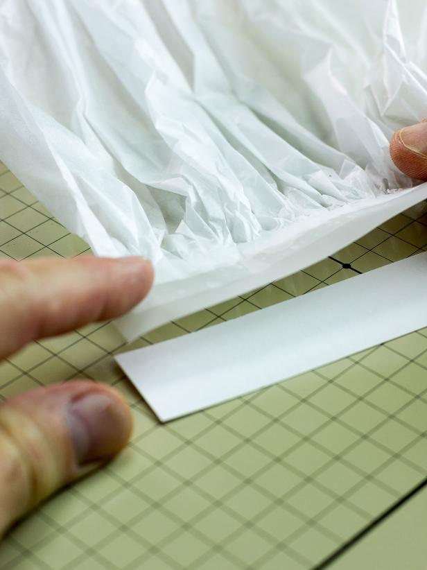 "Cut an 8-1/2"" by 1-1/8"" piece of card stock. Use another long piece of tape to attach one side of the pleated paper to the card stock. It should be positioned so the tape securing the pleated paper is completely attached to the card stock strip."