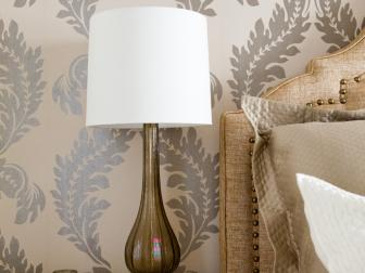 Off-white End Table with Blown-glass Lamp near Upholstered Headboard and Metallic-printed Wallpaper