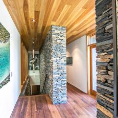 Modern Stairway Boasts Stacked Stone Wall & Wood Ceiling