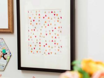 Geometric Framed Art With Pink, Orange and Neutral Triangles Over White Background in Black Frame With White Mat