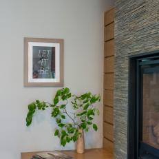 Contemporary Corner Display Featuring Rock Fireplace Surround, Built-In Wood Table and Simple Decor