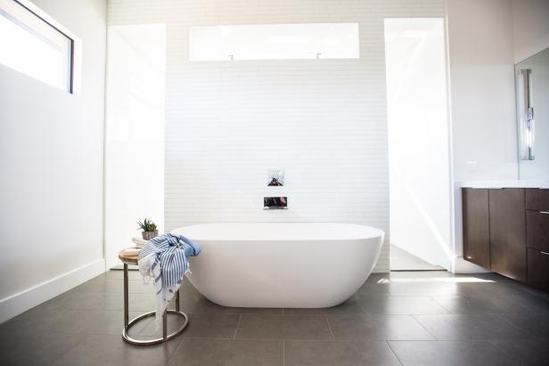 Large, minimalist bathroom with free-standing tub, in white.