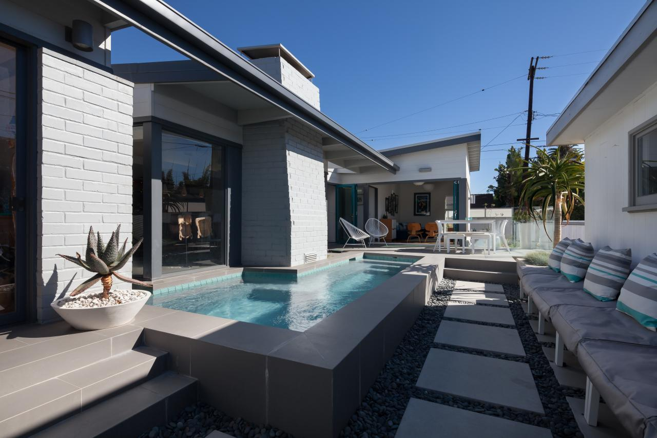 Modern Backyard With L Shaped Swimming Pool, Concrete Tile Walkway And Gray  Cushioned Seating With Striped Throw Pillows