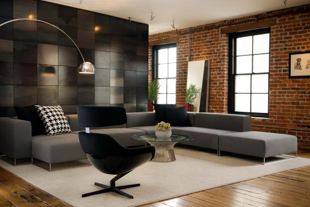Modern meets traditional in this urban loft space. A modern accent wall in shades of black and gray creates a separation from the home's other spaces. The structure's existing exposed brick wall brings a historical aura and industrial style. The large sectional sofa is sleek and streamlined, and the coffee table, chair and arc lamp add to the modern theme.