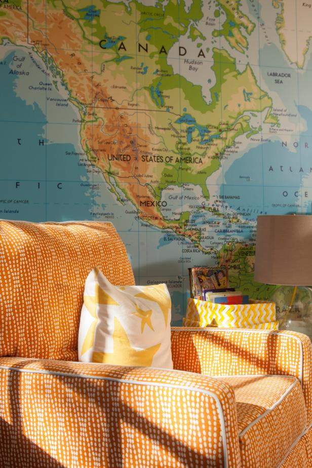 Wall Covered With World Map Behind Orange Patterned Armchair