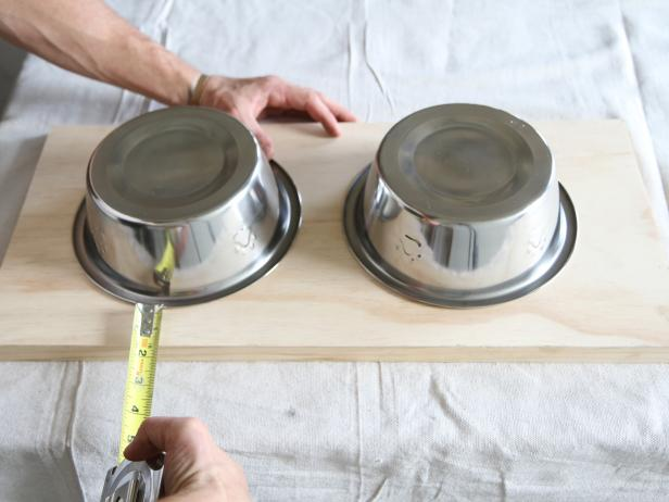 Place two stainless pet feeding bowls upside down on the wood stair tread, and measure to space them evenly.