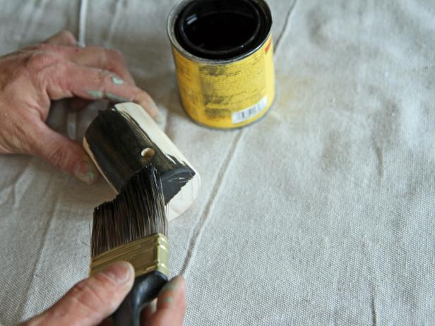 Apply ebony stain to the wood dowel, and let it penetrate for three minutes.