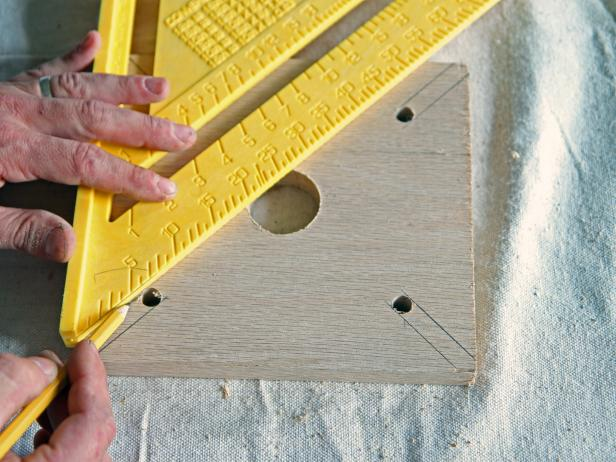 Use a square to draw a line on each side of the drilled holes to each of the corners of the wood block.