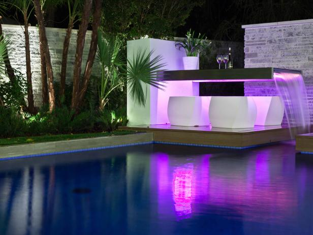 Night View of Swimming Pool With Purple Lighting and Water Feature