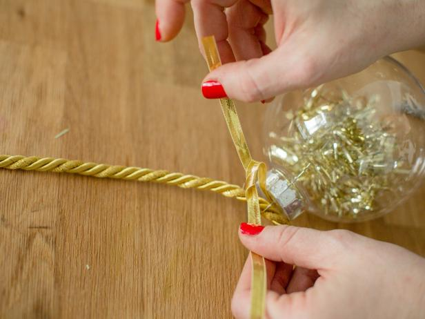 Once you have the ornaments prepped you can begin tying them onto the gold cord to create a garland. Tape one end of the cord to the table and slide ornaments on from the other direction toward the taped end. Secure the first ornament with a small piece of ribbon to keep it from sliding around. Do this every so often as you add more ornaments to the garland , then tie the very last ornament into place.