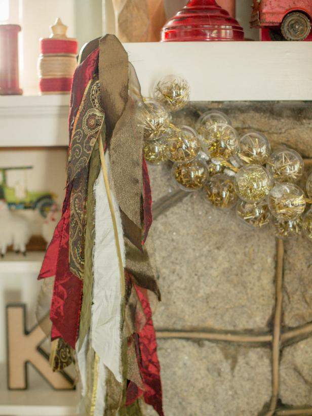 Knot the ends of the gold cord, then, using adhesive hooks and gold ribbon, hang the garland across the mantle horizontally. Next, hang the fabric swags on either side, vertically