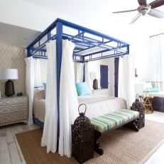 Bedroom With Large Blue Canopy Bed and Striped Bench