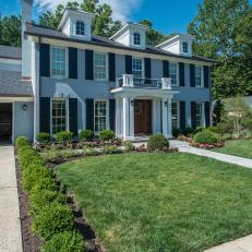 White Federal Two Story Home With Black Shutters and Boxwood Hedge