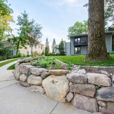 Lower Driveway View of Boulder Retaining Structure With Mulched Planter Section in Modern Home Backyard