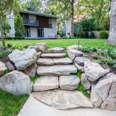 Boulder Steps Leading from Backyard to Concrete Walkway With Boulder Surrounded Mulched Planter Areas
