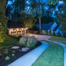Evening View of Descending Driveway With Garden Border Leading to Three Car Garage