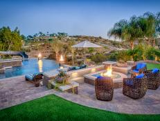 Tropical Pool Deck With Stone Fire Pit, Unique Wicker Chairs With Blue Cushions and Scenic View