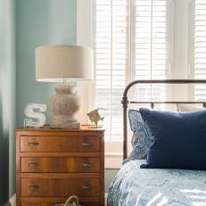 Blue Bedroom With Iron Bed, Dresser, White Lamp and Blinds