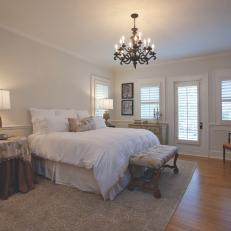 Traditional Bedroom With Tableclothed Nightstands, Plush White Bedding and Chandelier