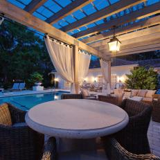 Luxurious Poolside Cabana With Privacy Curtains Shielding Wicker Seating and Concrete Tables