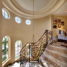 Spiral Staircase Showcasing Neutral Marble Tread and Small Tile Mosaic Risers