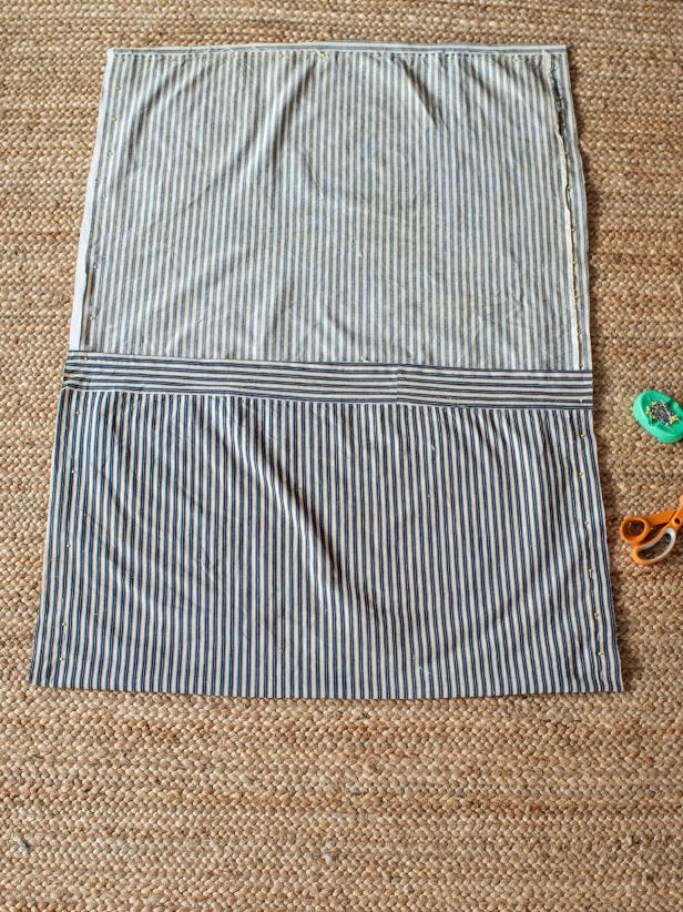 "Place top piece of fabric face up on floor or work surface.  Put ticking face down with extra material folded over. This excess fabric will be the ""envelope"" that holds the insert in place. Pin three sides together, leaving side with folded envelope closure open."