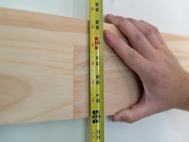 "Measure 60"" up from the floor with a measuring tape and mark with pencil.  This is the height of the bottom of the horizontal top rail."