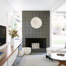 Global-Chic White Living Room Featuring Textured Fireplace Surround and Walnut Media Cabinet
