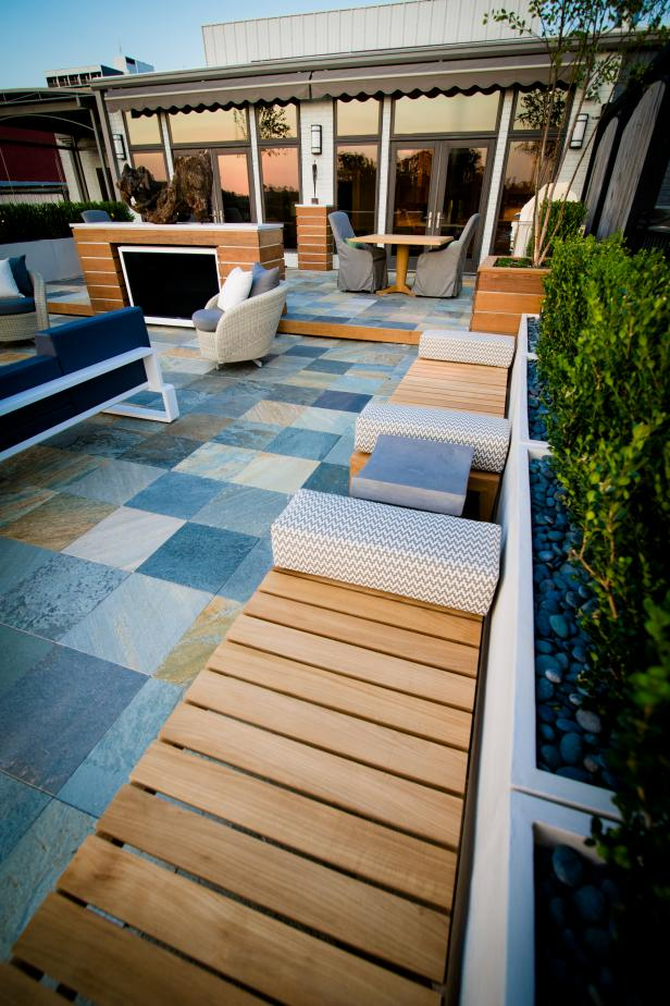 Wood-Slat Benches With Chevron Cushions on Stone Tile Patio