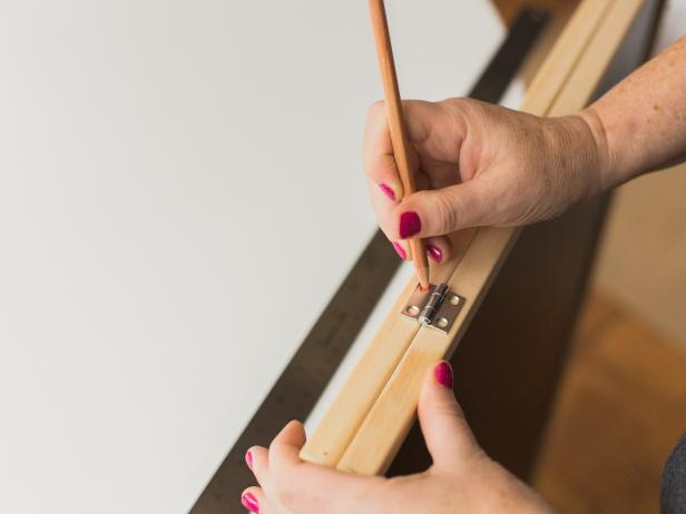 Line up the two chalk boards back-to-back, then mark the location of the two hinges four inches from the outside edge.