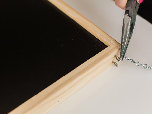 Using pliers, pry open the end links on both sections of jack chain. Take one chain's ends and connect it to the screw eyes on the right side of the chalkboard. Repeat this on the left side.