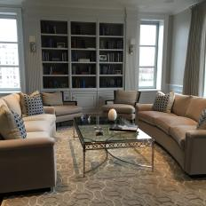 Transitional Living Room With Curved Neutral Matching Sofas, Traditional Glass Coffee Table and Built In Bookshelf