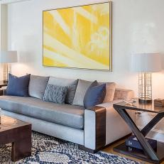 Contemporary Living Room Sofa Over Snakeskin Rug With Unique Wood End Tables and Sunny Yellow Artwork