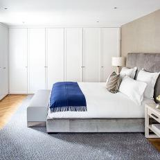 Classy, Minimalist Contemporary Bedroom With Thick Tufted Headboard, Royal Blue Accents and Large Closet Wall