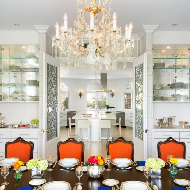 Lavish Transitional Dining Room With Crystal Chandelier Orange Chairs And Glass China Shelving