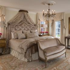 Victorian Master Bedroom With Plush, Neutral Bedding, Velvet Bench and Gold Highlights