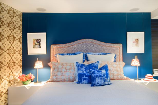 Blue and Orange Bedroom With Floral Wallpaper and Throw Pillows