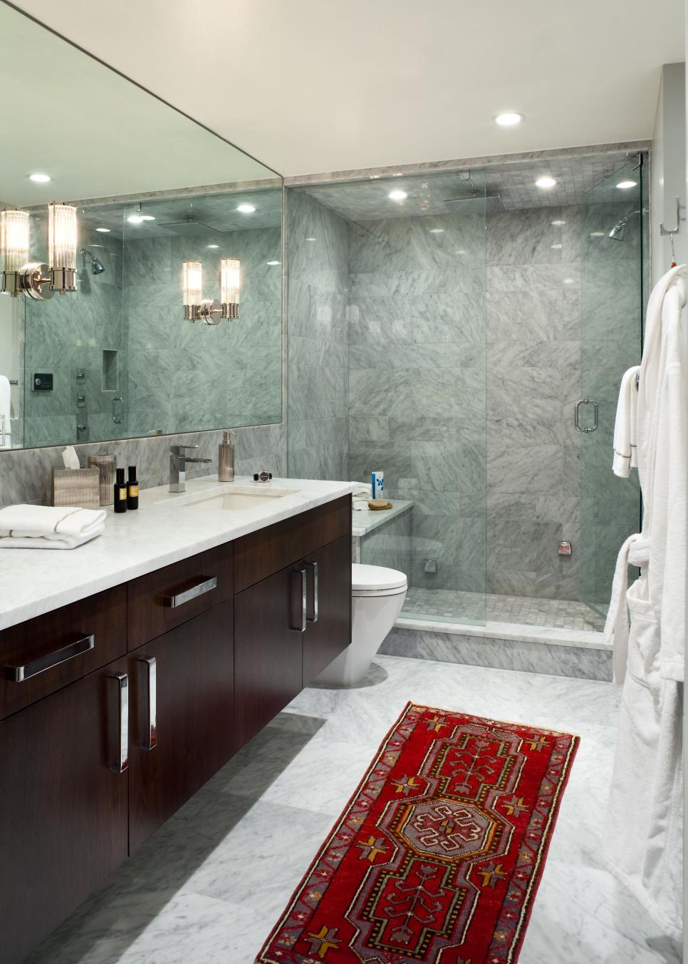 Gray Marble Bathroom With Glass Enclosed Shower And Red Rug