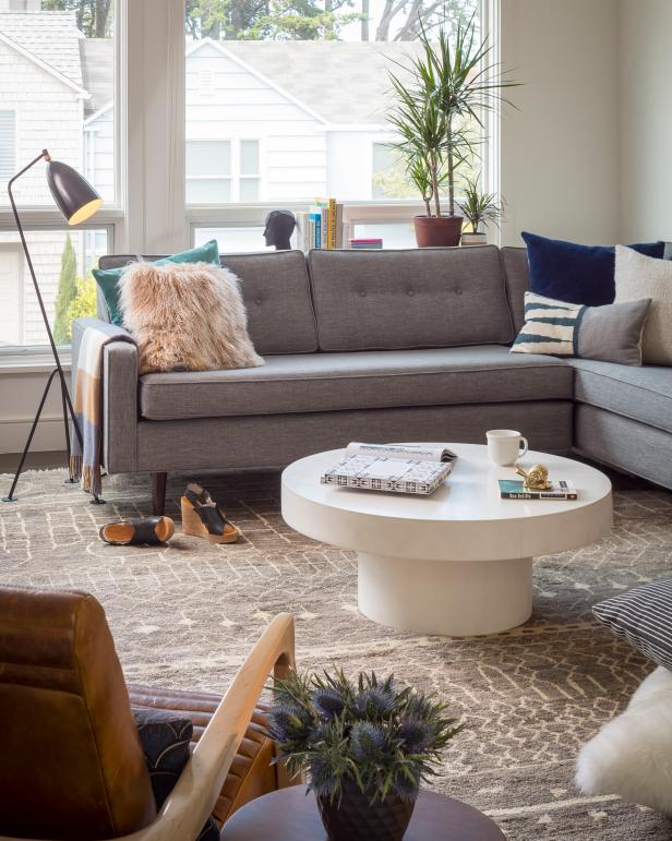 The upholstered gray sectional lends itself to effortless entertaining and family movie nights. Mismatched throw pillows in various colors and materials enhance the room's cozy, homey feel.