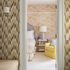 Patterned Wallpaper and marble Tile Floor Bathroom With View of Transitional Bedroom Featuring Yellow Accent Chair