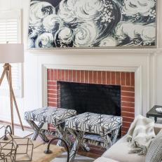 Brick Fireplace and Black and White Wave Mantel Artwork in Contemporary White Living Room With Upholstered Stools