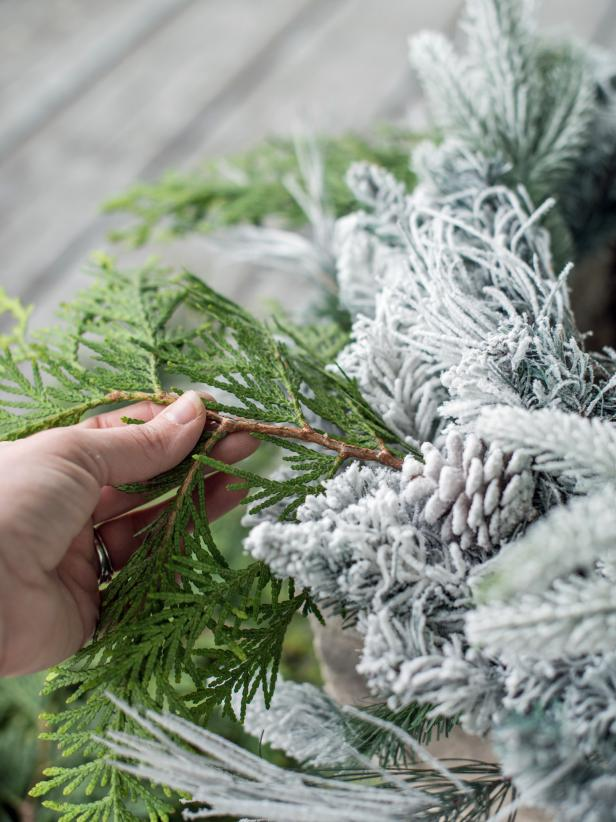 Step 2:  Assemble Greenery and SphereSet a wreath, top-side-up, on top of each urn or planter pot.  Tuck fresh or faux greenery, sprigs, sprays and/or berries into wreath.  Florists wire or hot glue can be used to secure sprigs, if necessary.  Set grapevine sphere on top of wreath, tucking battery packs inside of urn.  Turn on lights and enjoy the beautiful display that took only minutes to create!
