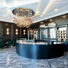 Art Decor Macaron Bakery With Dimensional Ceiling, Brass Chandelier, Crescent Counter and Black and White Floor