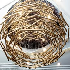 Ornamental Chandelier Made up of Layered Hanging Brass Rods in Decorative White Ceiling