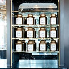 Flavor Jar Display Cabinet With Brass Trimmed Shelves and Mirror Background