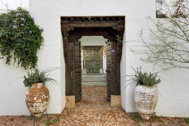 Asian Front Entryway With Elaborate Door Frame, Cobblestone Walkway and Large, Distressed Vases