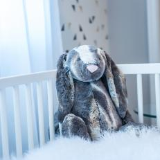 White Crib With Sheepskin Blanket In Nursery
