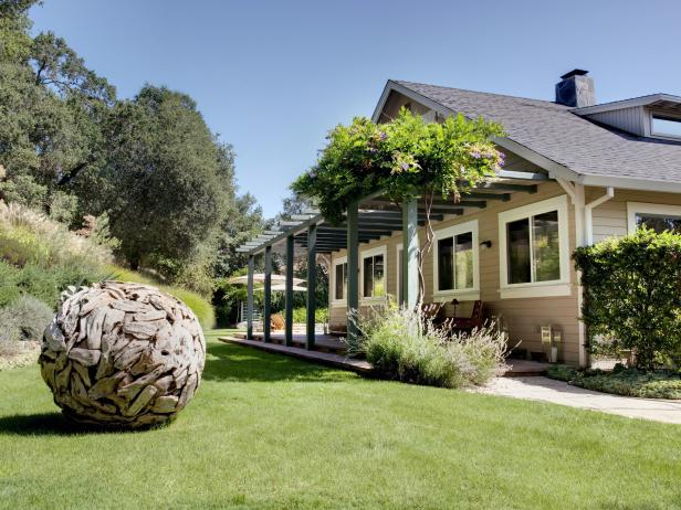 Cottage Front Yard With Pergola And Spherical Wooden Yard Art